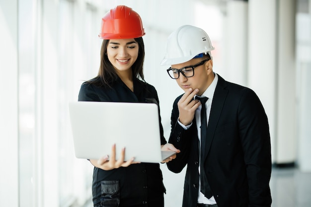 Mulher e homem empresário e arquiteto em hemlet em reunião de negócios, olhando para o laptop nas plantas de construção