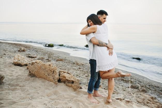 Mulher e homem estão abraçando na praia perto do mar