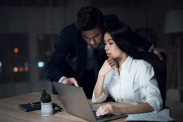Mulher e homem estão trabalhando até tarde no escritório escuro.