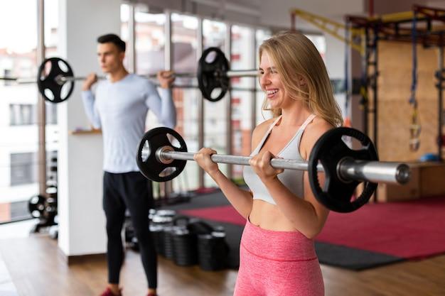 Mulher e homem fazendo musculação