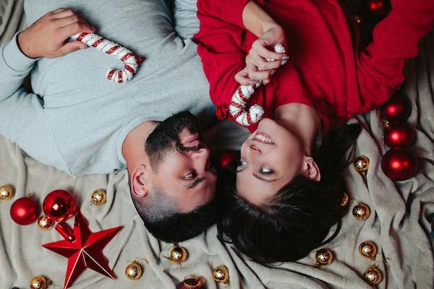 Mulher e homem feliz decoram a árvore de natal, homem e mulher segurar bastões de doces nas mãos.