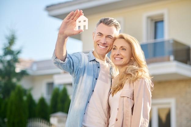 Mulher e homem felizes com sinal de casa