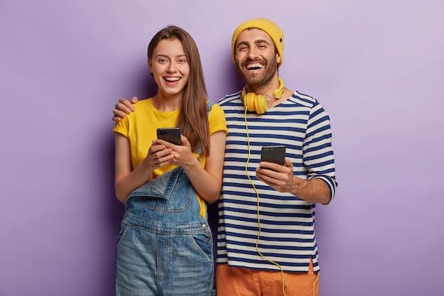 Mulher e homem felizes se abraçam e se divertem, usam tecnologias modernas, seguram smartphones