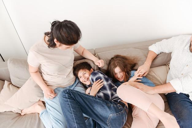 Mulher e homem felizes se divertindo e brincando com duas crianças, sentados no sofá juntos na sala de estar em casa