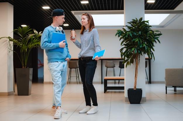Mulher e homem jovem e moderno na moda discutem um projeto conjunto no escritório