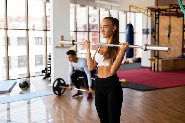 Mulher e homem levantando pesos exercício