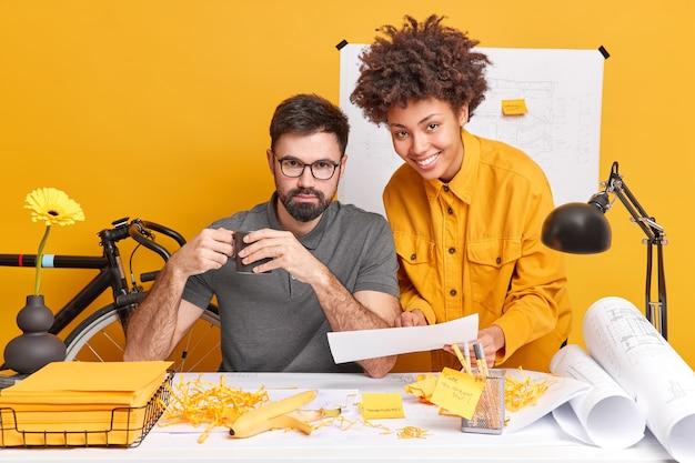 Mulher e homem mestiços colaboram juntos para discutir o projeto futuro e tentar encontrar a melhor variante para esboços posar em uma área de trabalho bagunçada
