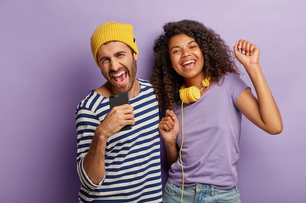 Mulher e homem milenar de raça mista radiante se divertem juntos, cantam alto e dançam ao som da música, usam tecnologias modernas para entretenimento