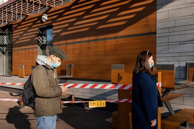 Mulher e homem na rua usando máscara
