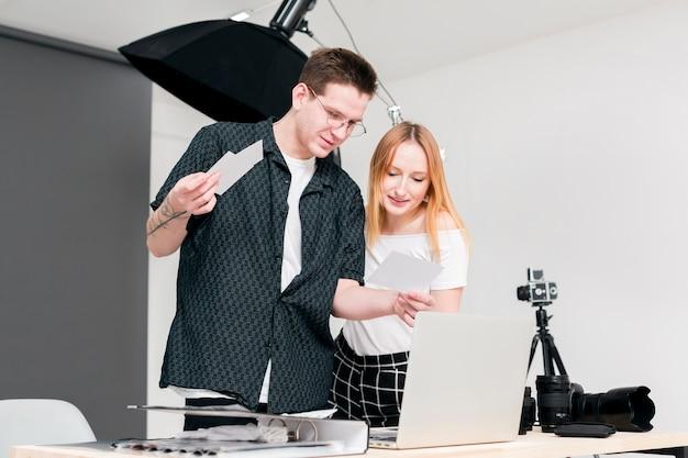 Mulher e homem olhando fotos em estúdio