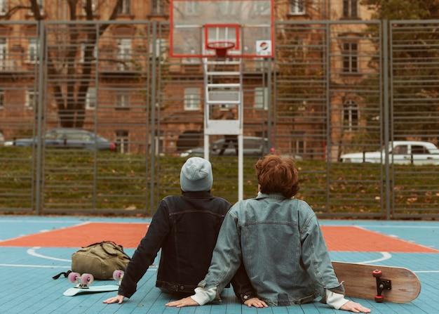 Mulher e homem olhando para um campo de basquete