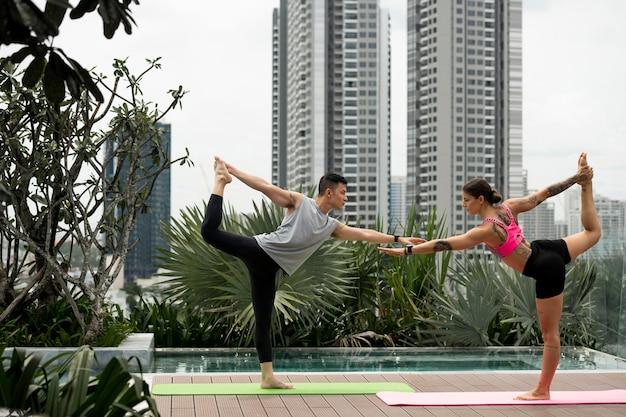 Mulher e homem praticando ioga no tapete ao ar livre ao lado da piscina