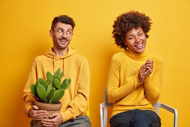 Mulher e homem riem e se divertem juntos posam em cadeiras em amarelo