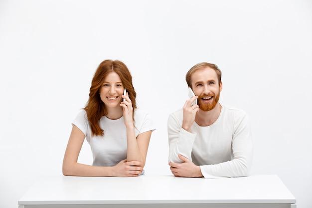 Mulher e homem ruiva feliz falam do telefone móvel