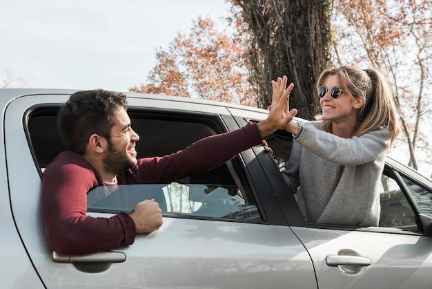 Mulher e homem saindo da janela do carro