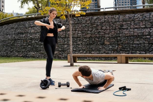 Mulher e homem se exercitando juntos ao ar livre