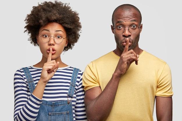 Mulher e homem secretos mostram sinal de silêncio, têm expressões de surpresa, tocam os lábios com os dedos indicadores