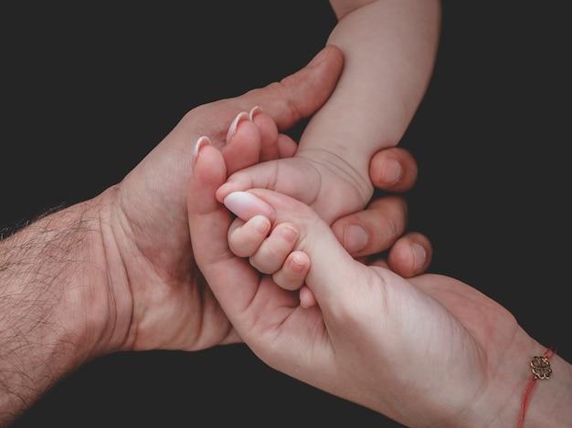 Mulher e homem segurando a mão do bebê recém-nascido