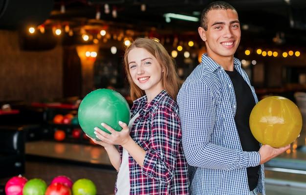 Mulher e homem segurando as bolas de boliche coloridas