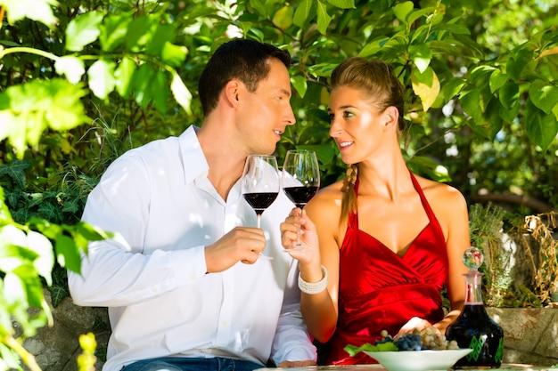 Mulher e homem sentado debaixo de videira e bebendo