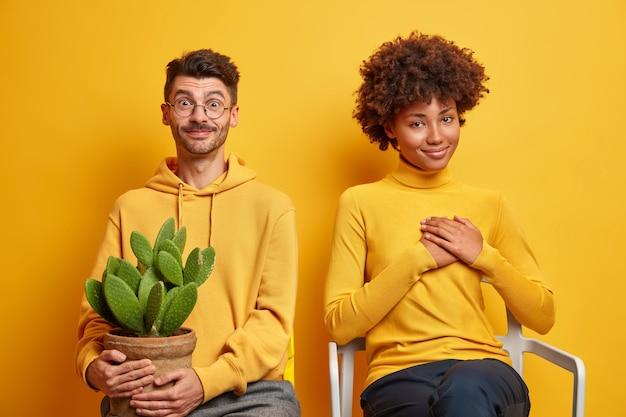 Mulher e homem sentam-se lado a lado em cadeiras confortáveis isoladas em amarelo