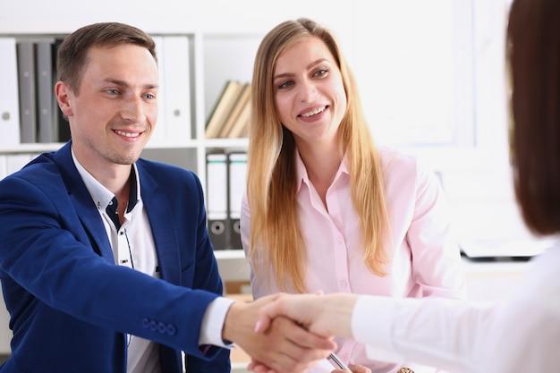 Mulher e homem sorridente apertam as mãos como olá no escritório