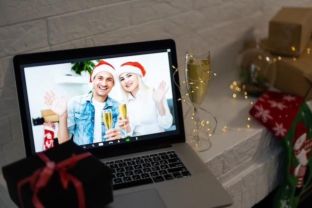Mulher e homem sorrindo em uma videochamada, ela está feliz e deseja um feliz natal online, com o interior do quarto decorado ao fundo