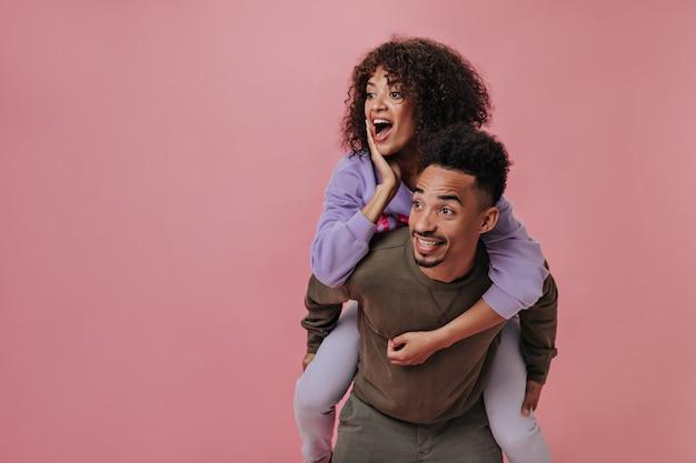 Mulher e homem surpresos posando na parede rosa
