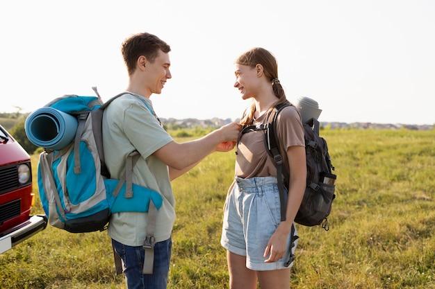 Mulher e homem tiro médio com mochila