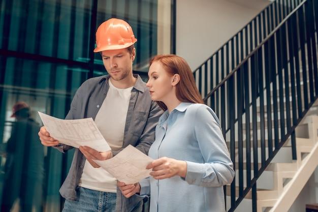 Mulher e homem trabalhando com plano de construção