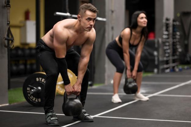 Mulher e homem treinando com pesos