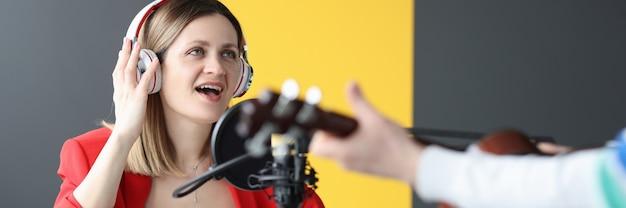 Mulher e homem usando fones de ouvido cantando e tocando violão trabalham como conceito de apresentador de rádio