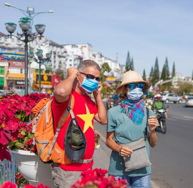 Mulher e homem vestindo máscara sanitária ao ar livre no centro da cidade da lat lat vietnã. proteção de máscara médica contra risco de novo vírus corona covid-19 na ásia