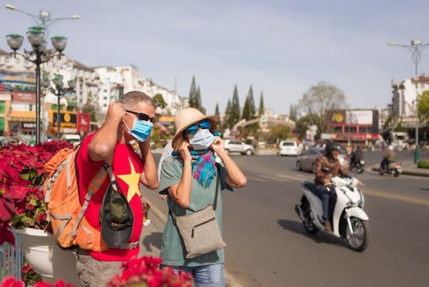 Mulher e homem vestindo máscara sanitária ao ar livre no centro da cidade da lat lat vietnã. proteção de máscara médica contra risco de vírus da gripe chinesa na ásia