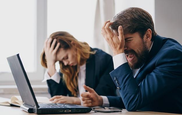 Mulher e homens de negócios se sentam em uma mesa de trabalho em frente ao escritório de emoções do laptop.