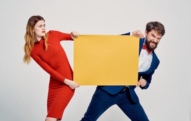 Mulher e homens enérgicos com folha de papel amarela anúncio de maquete de cartaz.