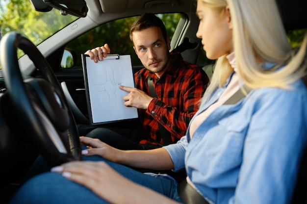 Mulher e instrutor com lista de verificação no carro, auto-escola. homem ensinando a senhora a dirigir o veículo.
