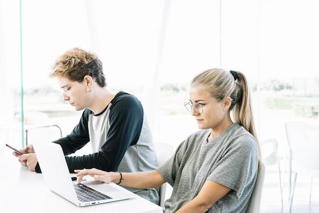 Mulher e jovem trabalhando lado a lado em uma mesa, um espaço de trabalho