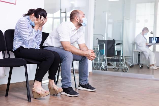 Mulher e marido chorando na sala de espera do hospital