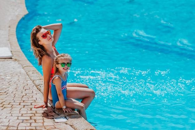 Mulher e menina bonitinha em biquíni de verão e óculos escuros posando juntas na piscina