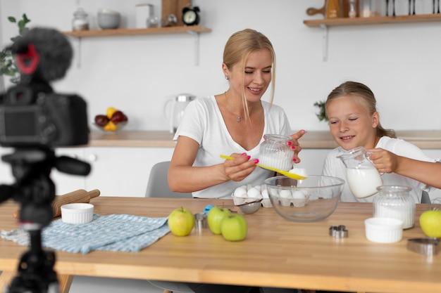 Mulher e menina cozinhando tiro médio