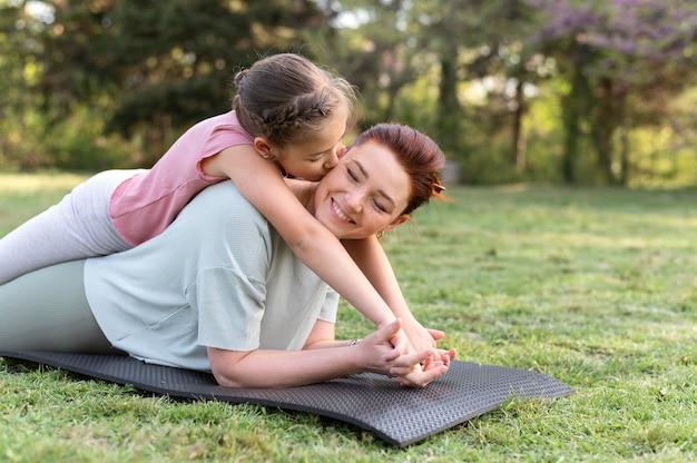 Mulher e menina em tiro médio em tapete de ioga