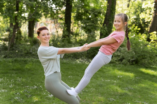 Mulher e menina em tiro médio praticando juntas