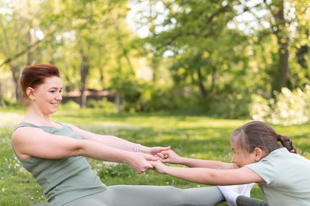 Mulher e menina em tiro médio se exercitando