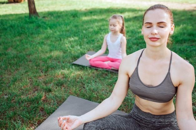 Mulher e menina estão meditando. eles estão sentados em posição de lótus e mantendo as mãos nos joelhos. eles estão concentrados e relaxados ao mesmo tempo.