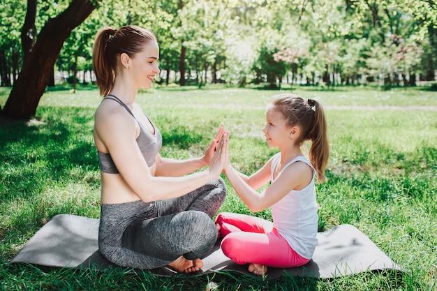Mulher e menina estão sentadas em carima cara a cara e olhando um ao outro. eles estão segurando um do outro. meninas estão sorrindo. eles parecem felizes. conceito de ioga e pilates.