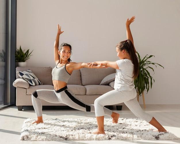 Mulher e menina fazendo esportes dentro de casa juntas