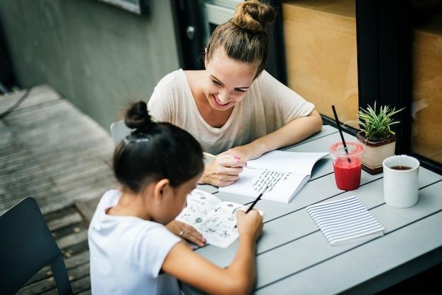 Mulher e menina fazendo o conceito de dever de casa