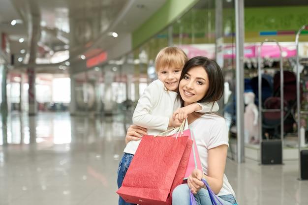 Mulher e menina felizes no levantamento, sorrindo no shopping.