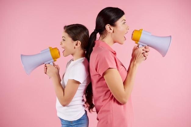 Mulher e menina gritando em megafones, em pé de costas